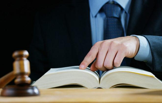 איש בחליפה קורא מתוך ספר ופטיש של שופט
